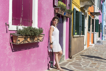 beautiful tourist woman with white dress walking in Burano ,Italy