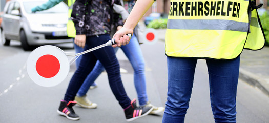 Schüler überqueren Übergang und Schülerlotse sichert Schulweg Banner