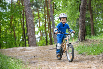 Happy funny little kid boy in colorful raincoat riding his first bike on cold day in forest. Active leisure for children outdoors. carefree childhood concept