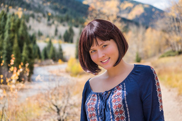 Portrait of young happy smiling woman by golden autumn river in Silverton, Colorado