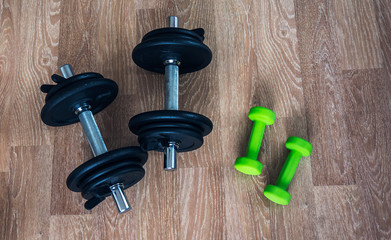 Bodybuilding concept. Two couple of dumbbells for men and women