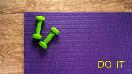 """Yoga mat and dumbbells with text """"do it"""". Motivation"""