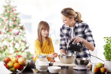 Mother and daughter at christmas.Portrait of cute daughter and her mom baking christmas cookies together in the kitchen.