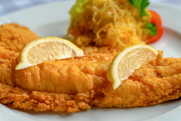 Fish dish - fried cod fish with lemon and sauerkraut.