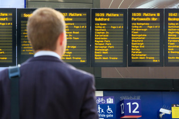 Deurstickers Treinstation Commuter checking digital timetables at a train station
