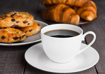 Cup of coffee with fresh scones and croissants