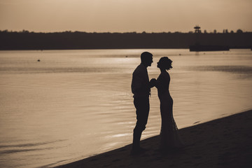Silhouette of sensual embracing young happy couple celebrating their love on the beach. Toned image