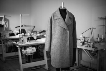 black and white photo with a coat on a mannequin in a sewing wor Wall mural