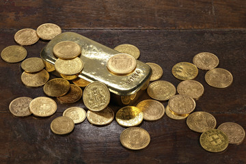 Goldbarren mit verschiedenen europäischen Goldmünzen aus dem 19./20. Jahrhundert auf rustikalem Holztisch