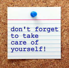 The words Don't Forget to Take Care of Yourself on a note card pinned to a cork notice board as a reminder to look after our own mental and physical health