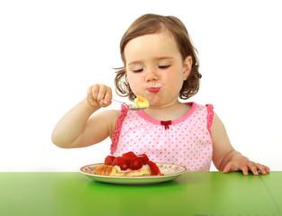 Ein dickes Kleinkind ißt ein Stück Erdbeertorte.