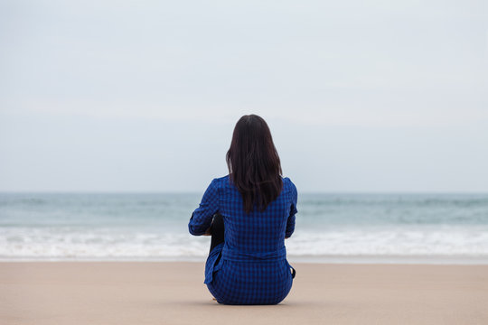 Lonely and depressed woman sitting on the sand of a deserted beach and watching the sea on an Autumn day.