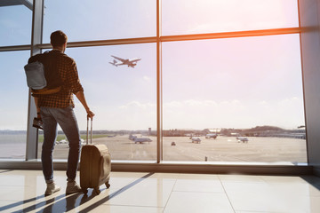 Wall Mural - Serene young man watching plane before departure