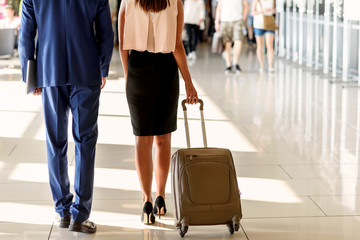 Businesspeople walking with luggage at airport