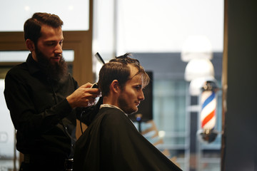 Barber man cutting a client's hair clippers in the barbershop