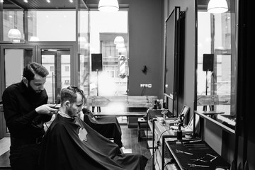 Barber man cutting a client's hair clippers in the barbershop black-and-white photo