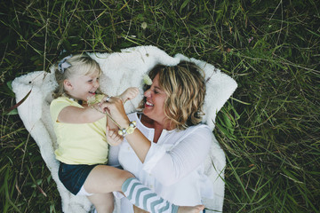 Woman and girl playing while lying in grass