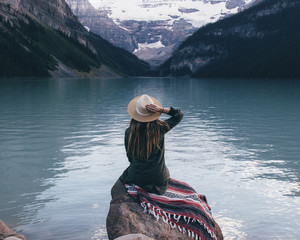 Rear view of woman sitting on rock and looking Lake Louise, Alberta, Canada