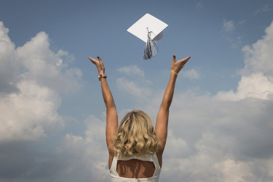 Rear view of happy woman throwing mortarboard