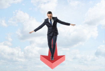 Businessman full-faced walking straight balancing on giant red arrow