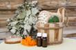 Деревянный ковш с предметами для купания, эфирные масла, мыло, расческа на фоне банного веника