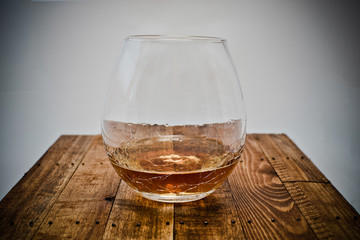a glass of brandy on wooden background