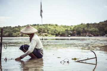 Fisherman working in river against sky