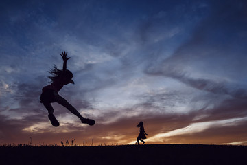 Silhouette sisters playing on field against dramatic sky during sunset