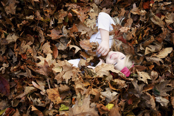 High angle view of cheerful girl lying in maple leaves during autumn