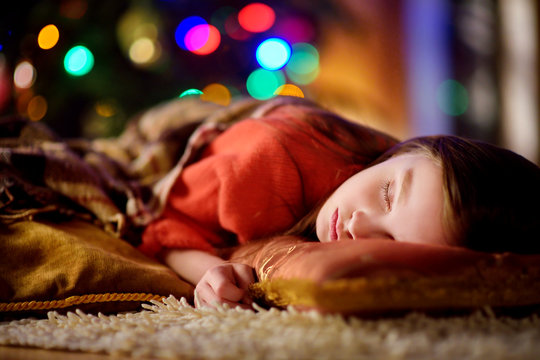 Adorable little girl sleeping under the Christmas tree by a fireplace