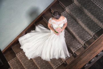 Looking down onto a bride sat on the stairs with her wedding dre
