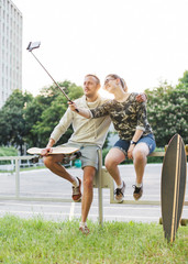 Couple with longboards making selfie