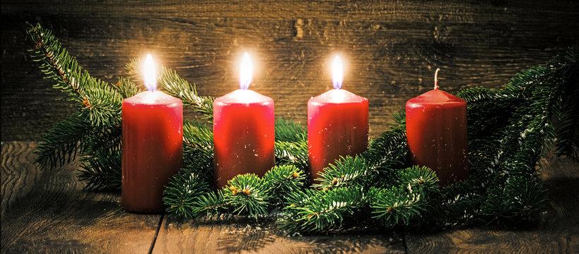 Dritter Advent: drei leuchtende Kerzen vor einem Holzhintergund