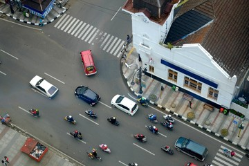 Traffic intersection with cars and motorcycles, in asia afrika street, bandung, Indonesia