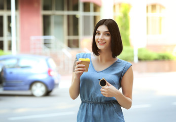 Young beautiful  girl  outdoors with cup of coffee