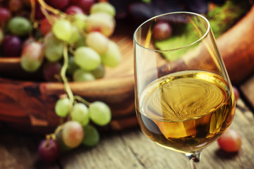Autumn ice wine, ripe grapes and dried leaves, vintage wooden ba
