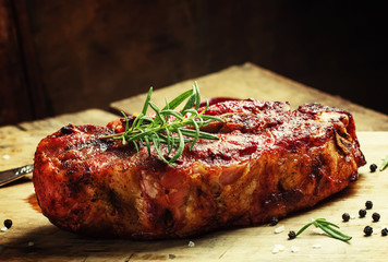 Aluminium Prints Grill / Barbecue Baked pork shoulder with pepper, rosemary and garlic, vintage wo