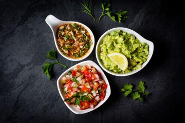 Traditional Latin American sauces Guacamole, Salsa, chili Pebre, slate background