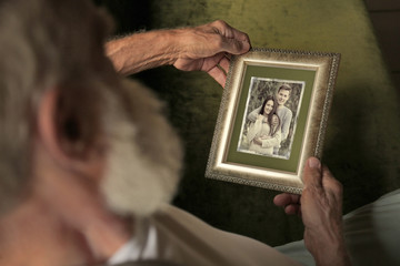 Elderly man holding photo frame with picture of young couple. Happy memories concept.