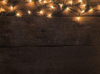 Frame of Christmas lights on old wooden desk background and empty space for text. Top view with copy space.