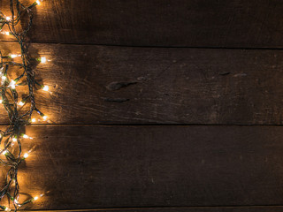 Christmas lights on vintage wooden desk background and empty space for text. Top view with copy space.