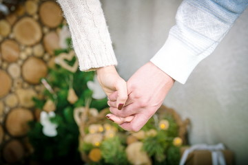 Two hands held together on the background of a winter home comfort. Love together, men's and women's hands with a house in winter evening