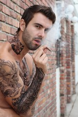 Portrait of sexy tattooed bearded man with a cigarette outdoors