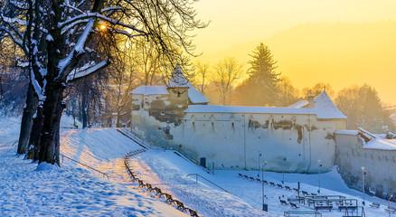 Wall Mural - Sunset light over weaver's bastion in winter season, Brasov, Transylvania landmark, Romania