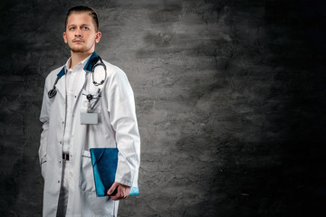 Studio portrait of young medical doctor holds blue clipboard on grey background.