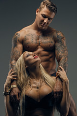 Tattooed male and sexy blonde female isolated on grey background