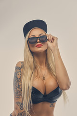 A woman with tattoo on her arm dressed in black bra.