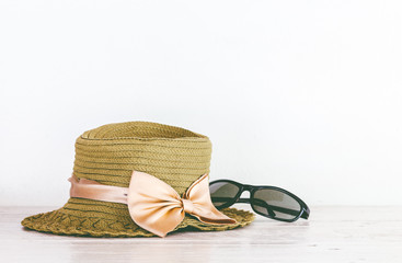 Hat and sunglasses on wooden table