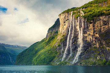 Geiranger fjord. Seven Sisters Waterfall, Norway. Mountain landscape with cloudy sky. Beautiful nature.