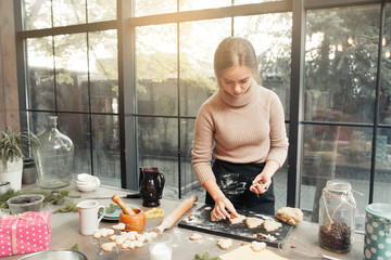 Woman decorating cookies before baking. Gingerbread treat preparing in for of Christmas tree with dried fruits and nuts decor